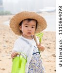 asian baby playing by the beach | Shutterstock . vector #1110864098