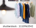 Stock photo clothes hang on wooden coat hangers in clothing store with home tone shopping and spending concept 1110963542