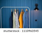 Stock photo clothes hang on wooden coat hangers in clothing store with home tone shopping and spending concept 1110963545