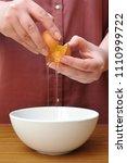 female hands separate the egg... | Shutterstock . vector #1110999722