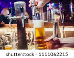 young woman dispensing beer in... | Shutterstock . vector #1111062215