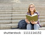 young smiling woman reading... | Shutterstock . vector #1111116152