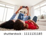 mother and son lying on rug and ... | Shutterstock . vector #1111131185