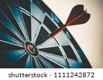 Stock photo close up shot of the dart arrow hit on bulleyes of dartboard to represent that the business reached 1111242872