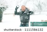 Small photo of Man with beard and shaved head is ready to throw a snowball in a park or forest during a big snowfall - winter 2018 2019