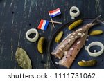Stock photo traditional dutch food herring with pickled cornichons and onion on dark blue ceramic plate and 1111731062