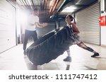 young muscular woman flipping a ... | Shutterstock . vector #1111747412