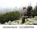 Small photo of Lost hiker in protective clothing in forest with mobile satellite navigation device - geo-caching