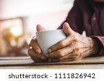 hands of old man holding cup of ... | Shutterstock . vector #1111826942