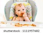 little baby eating her dinner... | Shutterstock . vector #1111957682