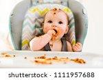 little baby eating her dinner... | Shutterstock . vector #1111957688