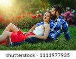 loving couple sitting down on... | Shutterstock . vector #1111977935