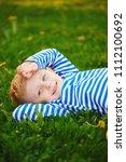little boy lying on the grass   Shutterstock . vector #1112100692