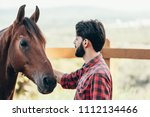 Small photo of Summer day on the farm. Young man caress horse