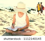 Small photo of child girl in hat writes draws dreams with sand on seashore in summer