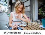 woman using phone in street cafe | Shutterstock . vector #1112386802