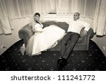 Bride with groom resting on the sofa - stock photo