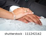 Married couple holding hands together with wedding rings - stock photo