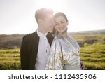 bride and groom at sunset in... | Shutterstock . vector #1112435906