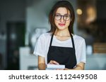 young waitress ready to take order on notepad in restauran