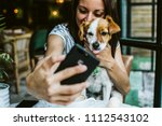 Stock photo young beautiful woman having great time with her little sweet dog in a restaurant after their meal 1112543102