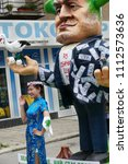 Small photo of Gabrovo, Bulgaria May 19, 2018. Traditional Carnival of Humor and Satire. Street art. A march of humorous models, masks and costumes. A Korean woman takes a picture in front of a model.