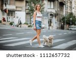woman and her pet dog walking... | Shutterstock . vector #1112657732