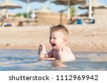 the boy is swimming in the sea. | Shutterstock . vector #1112969942