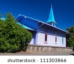 Blue and white wooden church against blue sky - stock photo