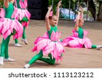 Small photo of Russia, Vladivostok, 06/12/2018. Nice little girls in funny costumes of lotus flowers perform the dance on stage. Celebration of annual Russia Day on June 12. Kids' performance. Show and performance.