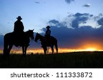 Cowboys On Horseback As Sun...