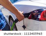man inserts the charger into an ... | Shutterstock . vector #1113405965