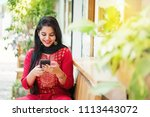 pretty young indian woman using ... | Shutterstock . vector #1113443072