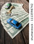 Small photo of Several 100 dollar banknotes with a home key and toy cars on the aged wooden surface. Illustration for: business success, private property, welfare, social inequality, fraud, corruption, mortgage.
