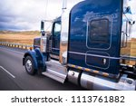 Dark blue shiny classic American big rig semi truck with chrome accessories with reflection on cab surface running on the road with yellow summer field on background in California - stock photo