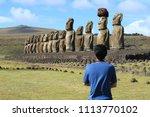 one man admiring the huge moai... | Shutterstock . vector #1113770102
