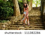 Portrait of a beautiful young woman, model of fashion, in a garden stairs - stock photo
