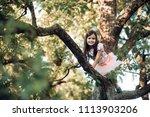 child smile on tree branch ... | Shutterstock . vector #1113903206