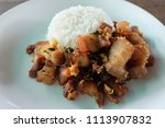 Small photo of Thai food. Rice topped with parch streaky pork with salt and chilly in white plate on wooden table.