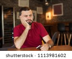 stressed man holding phone ... | Shutterstock . vector #1113981602