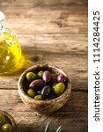 olives on olive branch. wooden...   Shutterstock . vector #1114284425