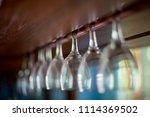 wine glasses hang on wooden bar | Shutterstock . vector #1114369502