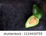 avocado with a stone on a dark... | Shutterstock . vector #1114410755