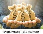 money bags in man hand show... | Shutterstock . vector #1114534085