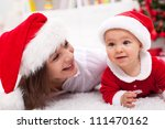 Our first Christmas - mother and baby with santa hats laying on the floor - stock photo