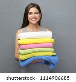 smiling woman holding pile of... | Shutterstock . vector #1114906685