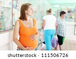 pregnant woman at the pharmacy drugstore - stock photo