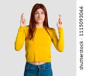 Small photo of Young redhead girl with yellow sweater with fingers crossing and wishing the best. Making a wish on grey background