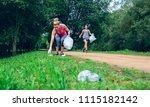 two girls picking up trash... | Shutterstock . vector #1115182142