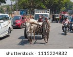 Small photo of Mysuru, India - March 3, 2018: A bullock cart making steady progress through the busy streets of central Mysore. Animal drawn vehicles are commonplace amidst motorized transport in Indian urban areas
